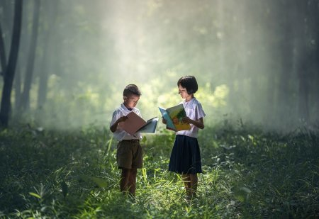 Children with books in woods and sunshine